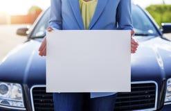 Автомобиль женщины готовя держа белый пустой плакат Стоковое Фото