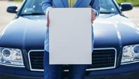 Автомобиль женщины готовя держа белый пустой плакат Стоковые Изображения