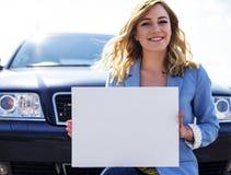 Автомобиль женщины готовя держа белый пустой плакат Стоковые Изображения RF