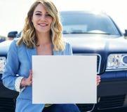 Автомобиль женщины готовя держа белый пустой плакат Стоковое Изображение