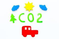 Автомобиль загрязняет окружающую среду углекислым газом Автомобиль, окружающая среда и вырез СО2 на белом взгляд сверху предпосыл Стоковое фото RF