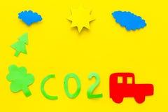 Автомобиль загрязняет окружающую среду углекислым газом Автомобиль, окружающая среда и вырез СО2 на желтом взгляд сверху предпосы Стоковая Фотография
