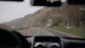 Автомобиль идет на шоссе в дожде в горной области Работая счищатели лобового стекла видеоматериал