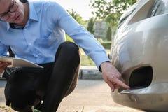 Автомобиль мужского агента рассматривая поврежденный дорожным происшествием кавказско стоковое изображение