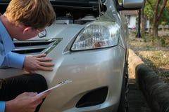 Автомобиль мужского агента рассматривая поврежденный дорожным происшествием кавказско стоковое изображение rf