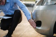Автомобиль мужского агента рассматривая поврежденный дорожным происшествием кавказско стоковая фотография rf