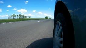 Автомобиль начинает двигать от обочины шоссе в сельской местности в солнечном летнем дне Камера установлена на стороне автомобиля сток-видео