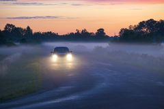 Автомобиль на дороге на заходе солнца Стоковое фото RF