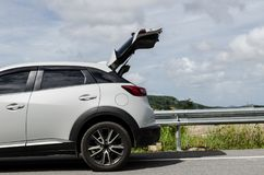 Автомобиль новой модели белый на дороге с предпосылкой стоковые фотографии rf