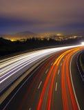 Автомобиль освещает на шоссе в направлении города стоковые фотографии rf