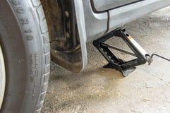 Автомобиль поднимает домкратом вверх для колеса изменяя или ремонтируя стоковое фото