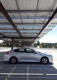 Автомобиль под панелями солнечных батарей стоковое изображение