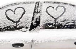 автомобиль покрыл снежок Сердца на покрытом снег автомобиле Сердце символ влюбленности Стоковое фото RF