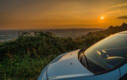 Автомобиль припарковал в улице с сногсшибательным взглядом на заходе солнца стоковые фотографии rf