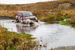 Автомобиль ралли 4x4 SUV преодолевает препятствие воды Стоковые Изображения RF
