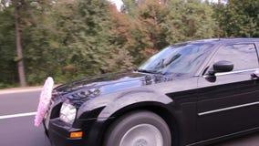 Автомобиль свадьбы с знаком сердца влюбленности управляет прочь на дороге акции видеоматериалы