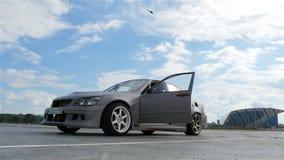Автомобиль спорт нижнего взгляда управляет и останавливает против неба с облаками сток-видео