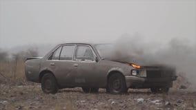 Автомобиль с горящим двигателем в поле, дыме приходит из-под клобука автомобиля сток-видео