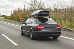 Автомобиль с контейнером коробки багажа крыши для перемещения на дороге Стоковые Фотографии RF