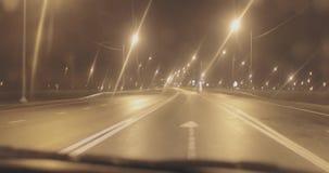 Автомобиль управляет на дороге асфальта вечером камера принимает ее с внутренности видеоматериал