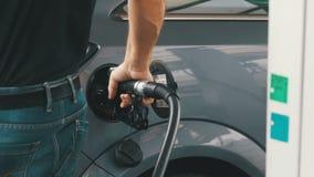 Автомобиль человека заполняя с дизельным топливом Укомплектуйте личным составом руку ` s используя бензонасос для того чтобы запо акции видеоматериалы