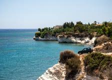 Автомобиль четырехколесного привода опасно припарковал рядом с крутой скалой на пляже ` s губернатора, Кипре Стоковые Фотографии RF