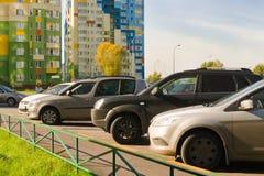 Автомобили автостоянки на обочине на предпосылке многоэтажных зданий в городе Стоковая Фотография RF