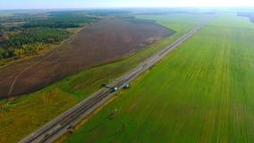 Автомобили взгляда неба управляют вдоль полей зеленого цвета прошлого шоссе Автомобильное движение Подъездная дорога автомобилей акции видеоматериалы