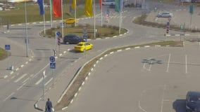 Автомобили двигают в круг, в месте для стоянки рядом с торговым центром Пестротканые флаги в ветре видеоматериал