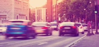 Автомобили двигая дальше городскую дорогу на сумрак стоковое изображение
