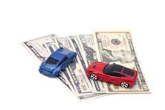 Автомобили игрушки красного конца голубые на банкнотах доллара изолированных на белизне Стоковые Изображения RF
