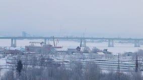 Автомобили идут на мост дороги над замороженным рекой с кораблями в снеге сток-видео
