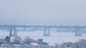 Автомобили идут на мост дороги над замороженным рекой видеоматериал