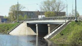 Автомобили идя на мост над малым рекой на солнечный день видеоматериал