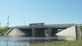 Автомобили идя на мост над малым рекой на солнечный день сток-видео
