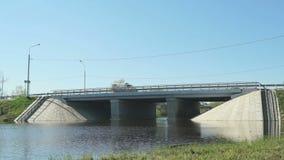 Автомобили идя на мост над малым рекой на солнечный день акции видеоматериалы