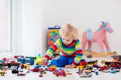автомобили мальчика меньшяя играя игрушка Стоковое фото RF