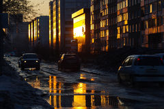 Автомобили на улице города на лучах захода солнца отразили в spri Стоковые Фото