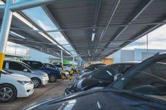 Автомобили паркуя в автостоянке на день Стоковые Изображения RF