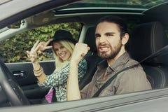 Автомобили - пары управляя в новый усмехаться автомобиля счастливый, смотрящ камеру Стоковые Изображения