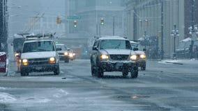 Автомобили проходя на дорогу города с падать снега сток-видео
