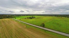 Автомобили проходя управлять к горизонту Зеленые поля и облака Воздушный отснятый видеоматериал акции видеоматериалы