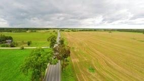 Автомобили проходя управлять к горизонту Зеленые поля и облака Воздушный отснятый видеоматериал сток-видео