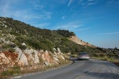 Автомобиль бежать быстро на изогнутой опасной дороге горы Стоковые Фото