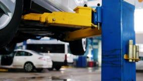 Автомобиль в автоматическом обслуживании поднимаясь для ремонтировать, механики в гараже акции видеоматериалы