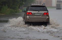 Автомобиль едет в проливном дожде на затопленной дороге Стоковая Фотография