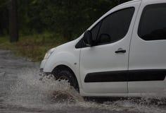 Автомобиль едет в проливном дожде на затопленной дороге Стоковые Изображения