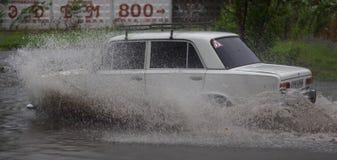 Автомобиль едет в проливном дожде на затопленной дороге Стоковое Фото