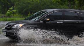 Автомобиль едет в проливном дожде на затопленной дороге Стоковое фото RF