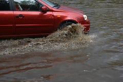 Автомобиль едет в проливном дожде на затопленной дороге Стоковое Изображение